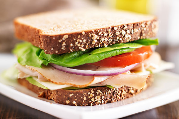 Sandwich with lettuce, turkey, and tomato on an office desk